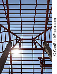metal structure of house roof in home construction site and sun shining on blue sky use for construction business and construction industry