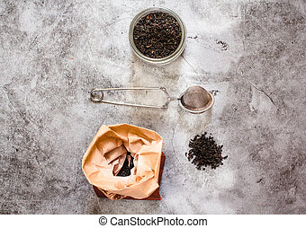 Metal thermos and tea infuser. Black tea in a jar and a paper bag. Zero waste plastic free kitchen on gray background. concept sustainable lifestyle or Recycling and ecology
