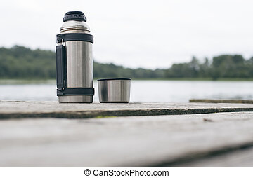 Metal thermos on the old wooden bridge, close-up
