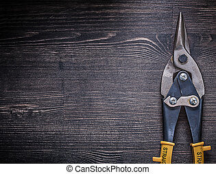 Metal tin snips on wooden board copyspace construction concept.
