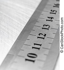 Metal tools. Ruler on the scratched metal background.