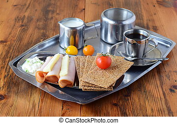 Metal tray with crispbread, cheese, cottage cheese, ham, cherry tomato, cup of coffee, sugar jar, creme jar on a wooden background. Healthy breakfast. Healthy eating.