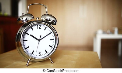 Metal vintage alarm clock counting standin on table indoors