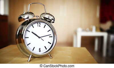 Metal vintage alarm clock counting standin on table indoors,...