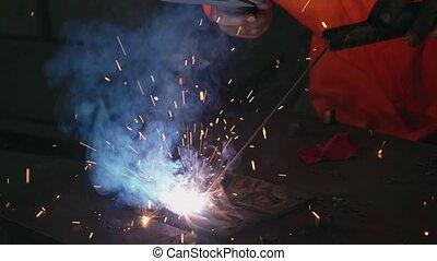Metal welder working with arc welding machine to weld steel ...
