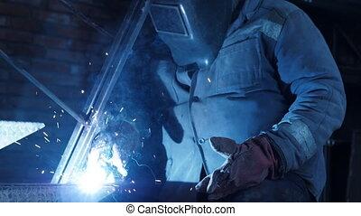 Metal welding close-up. Male welder working in protective...