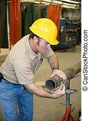 Metal Worker Measures Pipe