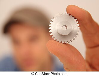 metal, worker presenting a gear wheel