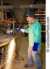 Metal Worker Using Track Burner - Metal worker in a factory...