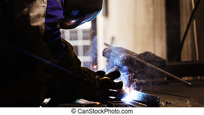 Metal worker welding in metal industry factory