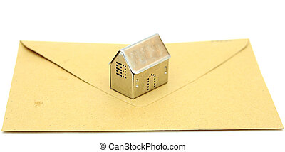 metall house shaped object on brown envelope