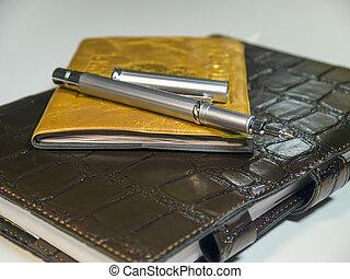 Metallic ball pen on notebook closeup