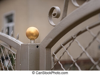 Metallic fence post with a golden ball on top