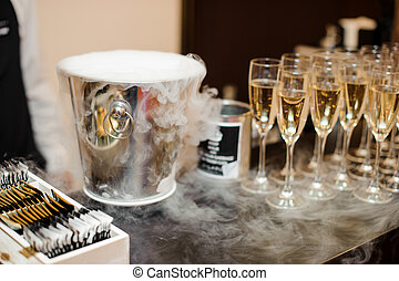 Metallic ice bucket and set of glasses filled with champagne