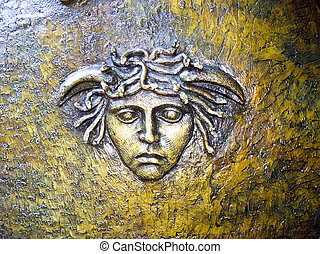 Fabled Medusa head with snakes on metal
