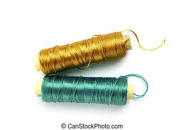 metallic rayon thread line spool in green and golden colors over white