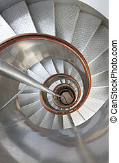 Metallic spiral stair with wooden handrails inside a lighthouse. Vertical
