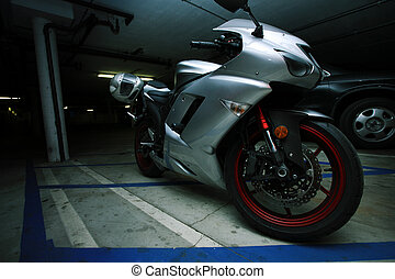 Metallic sport motorcycle parked in garage structure