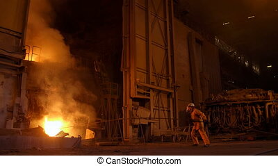 Metallurgist at work by the blast furnance, iron and steel...