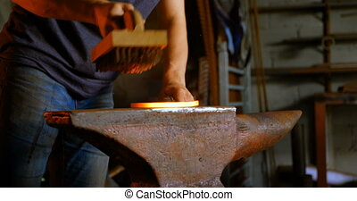 Metalsmith brushing horseshoe in fire 4k - Mid section of ...