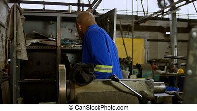 Metalsmith looking at tools in cupboard 4k - Attentive ...