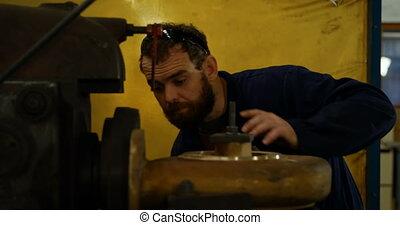 Metalsmith operating machine in workshop 4k - Attentive ...