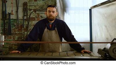 Metalsmith standing in workshop 4k - Portrait of metalsmith ...