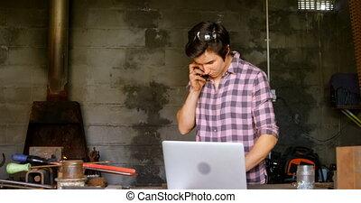 Metalsmith talking on mobile phone while using laptop 4k - ...
