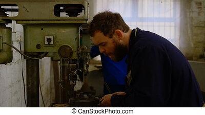 Metalsmith using drill press machine in workshop 4k - ...