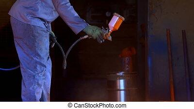 Metalsmith using spray painting machine in workshop 4k - ...