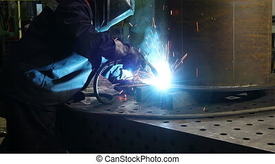 Metalworker in safety mask and gloves using welding torch to join sides of metal construction