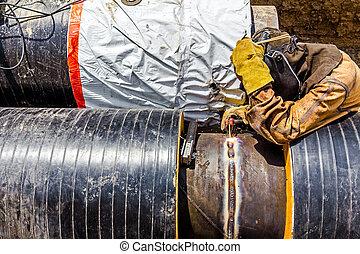 Metalworker working on a pipeline - Welder is welding a pipe...
