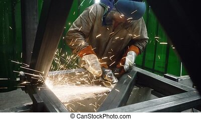 Metalworker working with angle grinder, lots of sparks...
