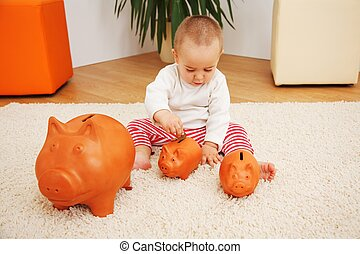 Little baby boy sitting and inserting coint into piggy bank; metaphoric view of the early savings, insurance or investments