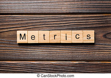 METRICS word written on wood block. METRICS text on wooden table for your desing, concept