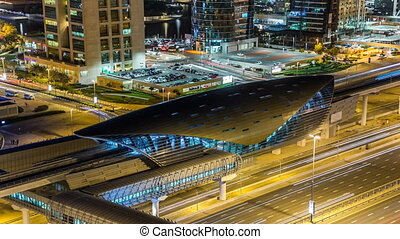 Metro station near Buildings of Jumeirah Lakes Towers with traffic on the road night timelapse.