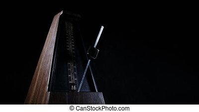 Slow motion shot of vintage metronome with golden pendulum beats slow rhythm on the dark background