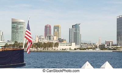 Metropolis urban skyline, highrise skyscrapers of city downtown, San Diego Bay, California USA. Waterfront buildings near pacific ocean harbour. Star-Spangled Banner, Old Glory national flag waving.