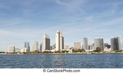 Metropolis urban skyline, highrise skyscrapers of city downtown, San Diego Bay, California USA. Waterfront buildings near pacific ocean harbour. View from boat, nautical public transport to Coronado.