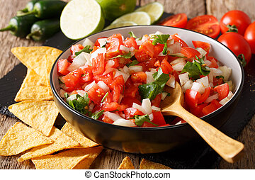 Mexican appetizer Pico de Gallo close-up in a bowl....