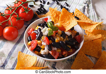 Mexican cuisine: tasty salsa and corn chips nachos close-up....