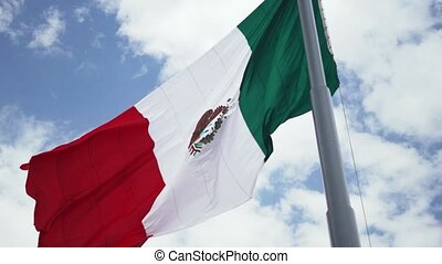 4K view of the mexican flag waving in the wind with a cloudy sky as background