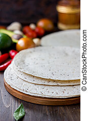 Mexican flatbread tortilla on wooden background.