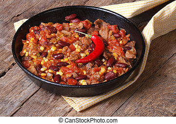 Mexican food is chili con carne in a frying pan on a wooden...