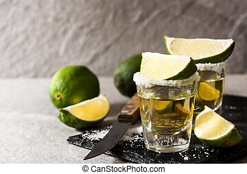 Mexican Gold tequila with lime and salt on black background. Copyspace