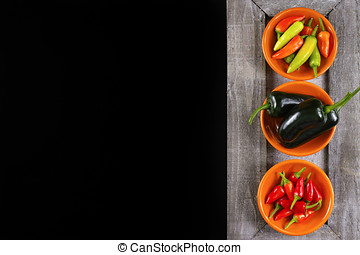 Mexican hot chili peppers colorful mix jalapeno on orange bowls