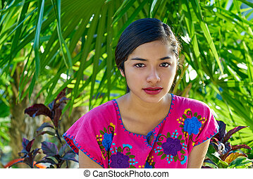 Mexican latin woman with mayan dress in the jungle