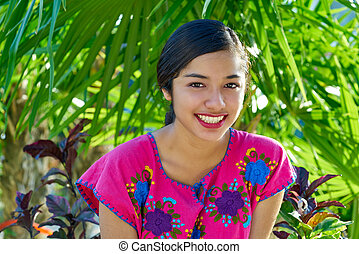 Mexican latin woman with mayan dress smiling in the jungle