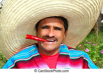 Mexican man poncho sombrero eating red hot chili - Mexican...