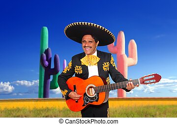 Mexican mariachi charro playing guitar in cactus